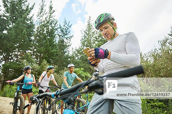 Man mountain biking  using smart phone in woods