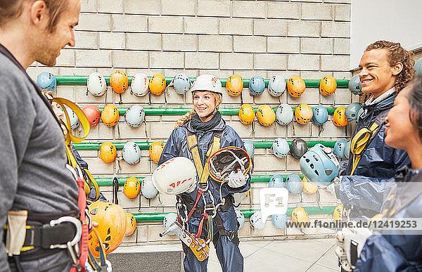 Friends preparing zip line equipment  putting on helmets