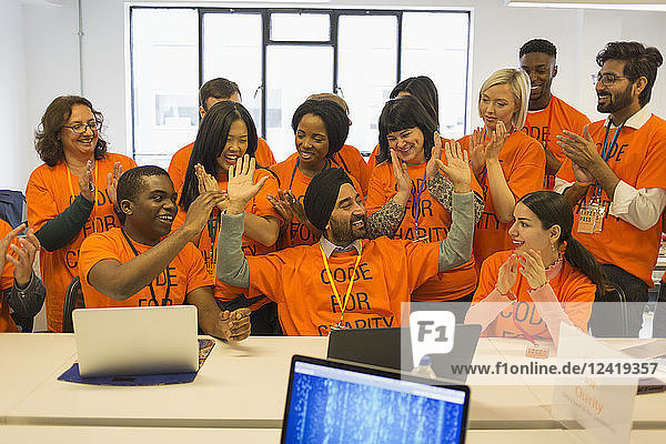 Enthusiastic hackers celebrating  coding for charity at hackathon