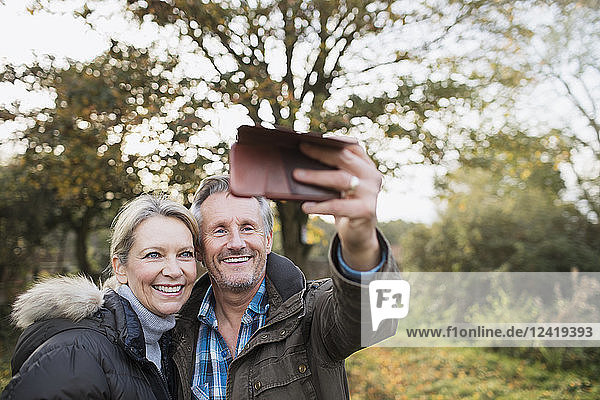 Happy mature couple taking selfie with camera phone in autumn woods