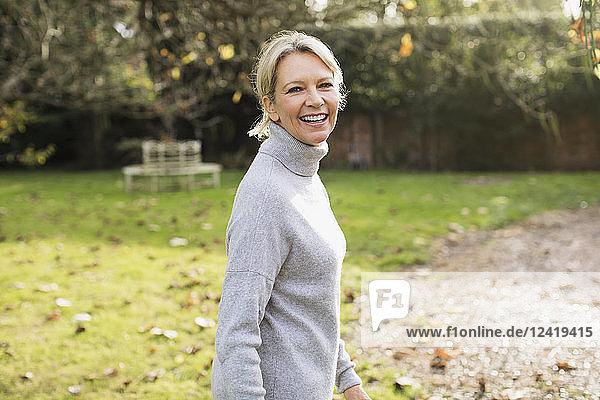 Portrait smiling  confident mature woman in sunny autumn backyard