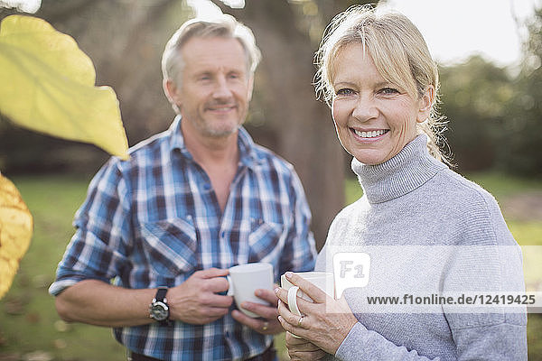 Portrait smiling  happy mature couple drinking coffee in backyard