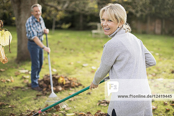 Portrait happy mature woman raking autumn leaves in backyard