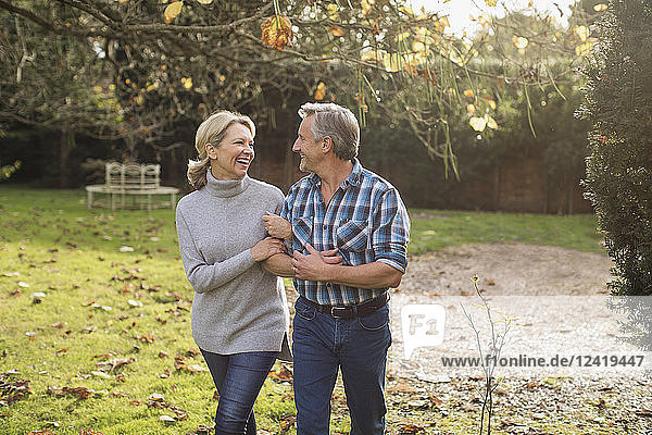 Happy  carefree mature couple walking arm in arm in sunny autumn backyard