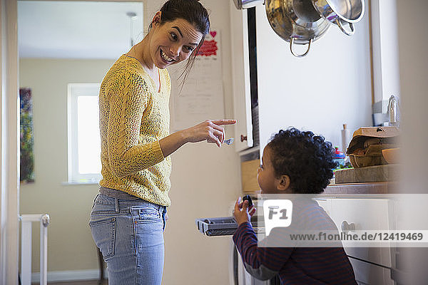 Playful mother and son in kitchen