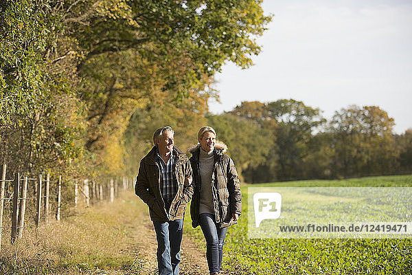 Mature couple walking arm in arm in sunny  rural autumn field