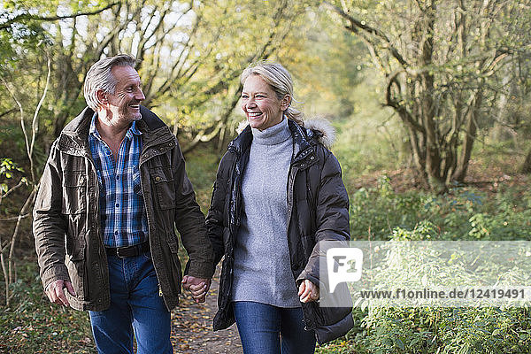Happy  affectionate mature couple holding hands and walking in autumn park