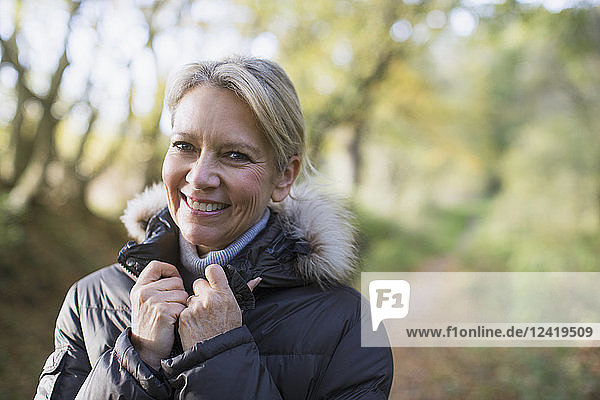 Portrait smiling  confident mature woman in parka in woods