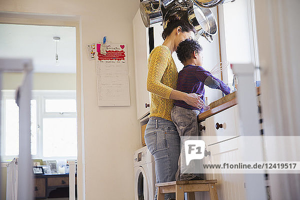 Mother and toddler son on stool doing dishes at kitchen sink