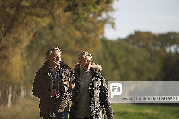 Mature couple walking arm in arm in sunny autumn park
