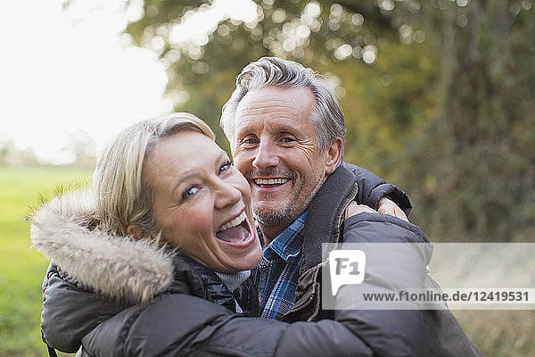 Portrait happy mature couple hugging in park