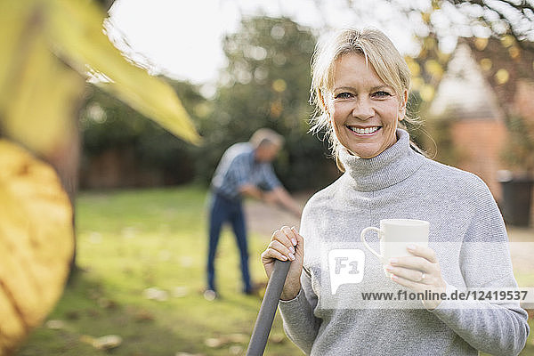 Portrait smiling  confident mature woman drinking coffee and raking autumn leaves in backyard