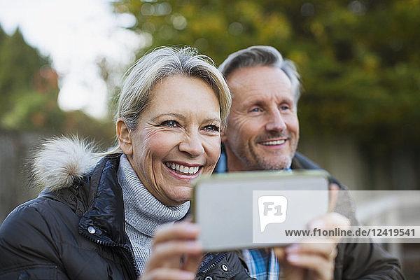 Happy mature couple using camera phone