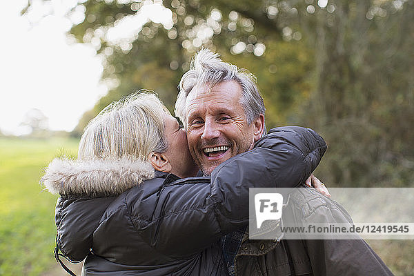 Portrait happy  playful mature couple hugging in park