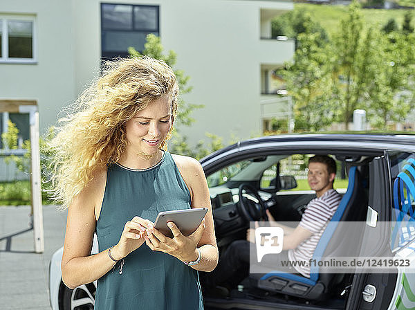 Smiling young woman using tablet with man sitting in electric car in background