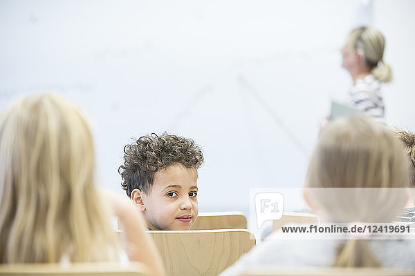 Portrait of schoolboy with classmates and teacher in class