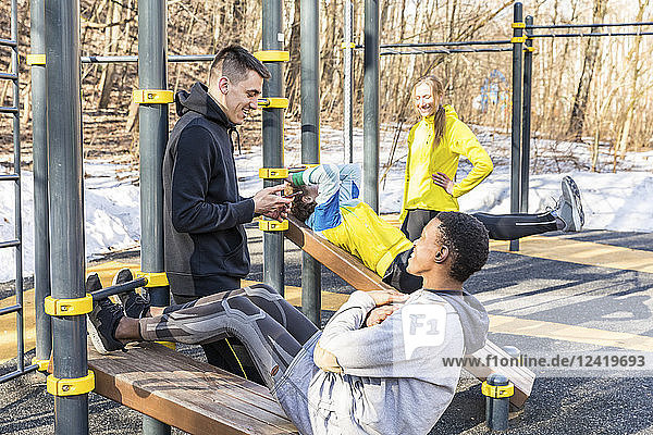 Friends exercising at fitness equipment in a park