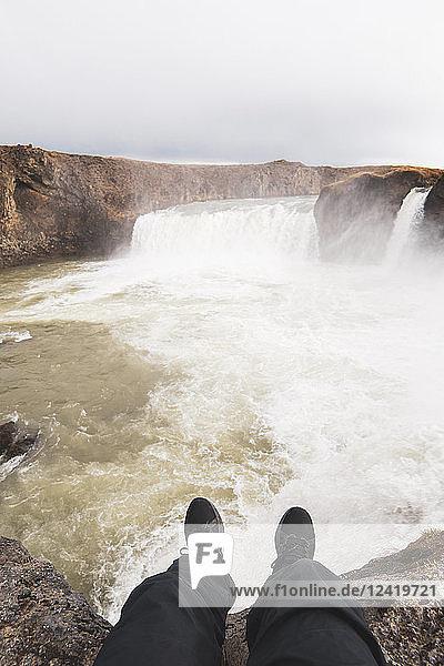 Iceland  legs of a man sitting at Godafoss waterfall