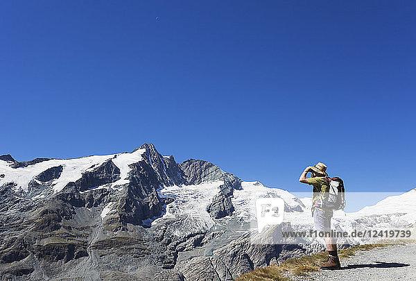 Austria  Carinthia  man  hiker with binoculars watching Grossglockner peak  High Tauern National Park