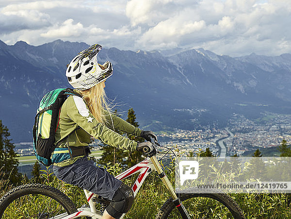 Austria  Tyrol  female downhill mountain biker looking into valley