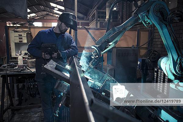 Welder welding metal with robot