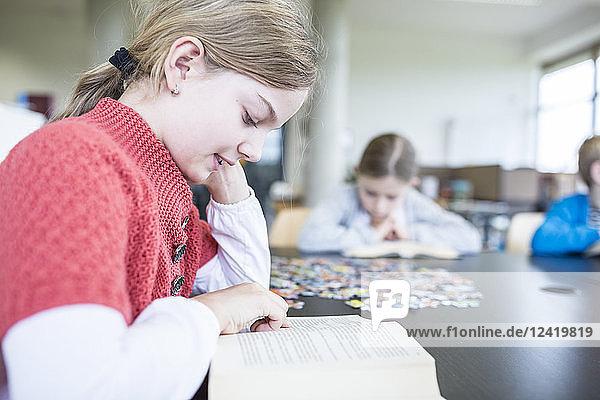 Schoolgirl reading book on table in school break room