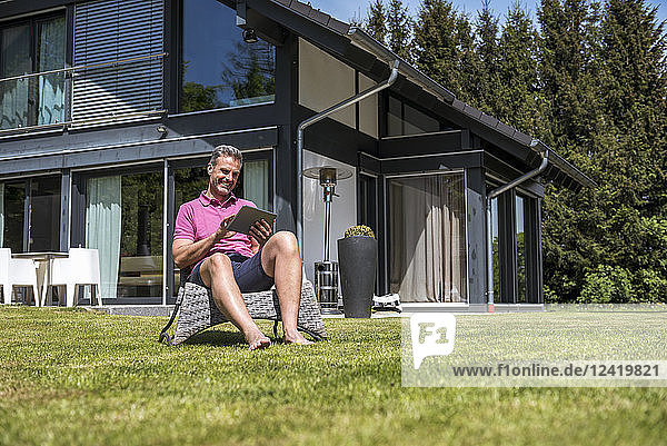 Smiling mature man sitting in garden of his home using a tablet