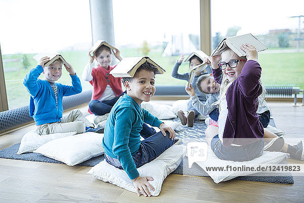 Smiling pupils sitting on the floor in school break room balancing books on their heads