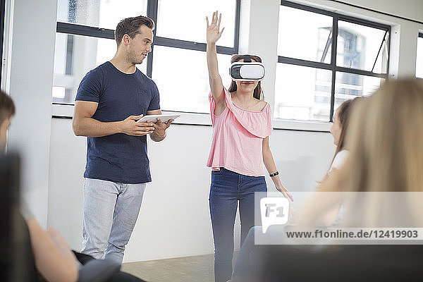 Teacher with tablet student wearing VR glasses in class