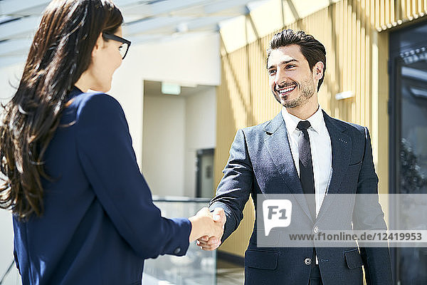 Smiling businessman and businesswoman shaking hands in office