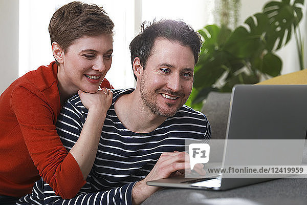 Couple sitting at home  using laptop
