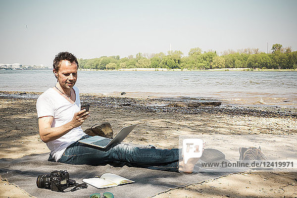 Man sitting on blanket at a river using laptop and cell phone