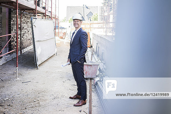 Smiling architect wearing hard hat standing on construction site