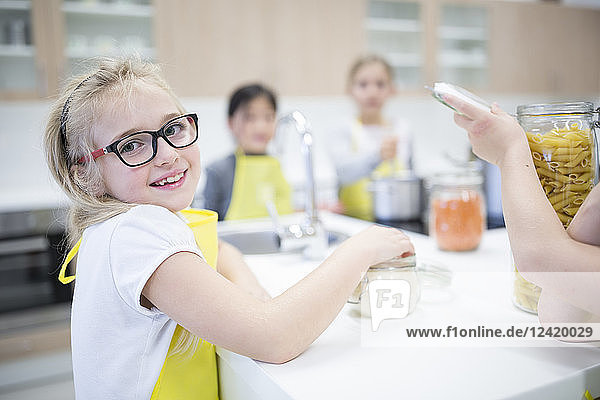Portrait of smiling schoolgirl with classmtes in cooking class