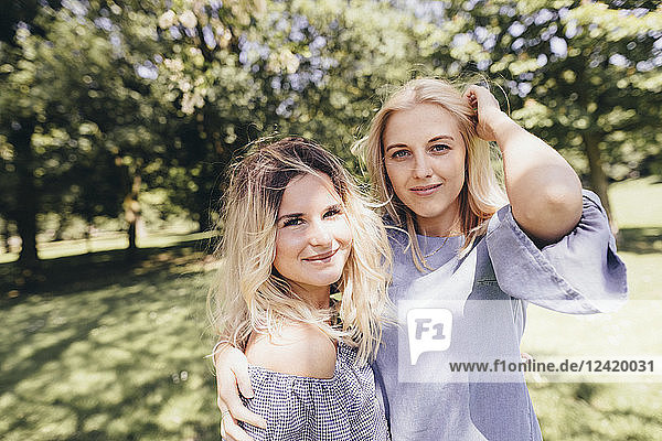 Portrait of two smiling young women embracing in a park