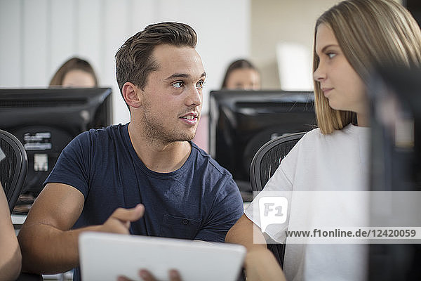 Teacher talking to student in computer class