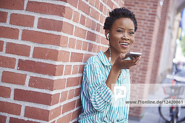 Portrait of smiling woman with earphones on the phone Portrait of smiling woman with earphones on the phone