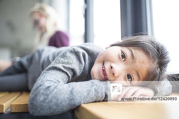 Portrait of smiling schoolgirl lying on bench in school