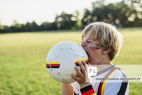 Boy with face paint and German football shirt  biting soccer ball