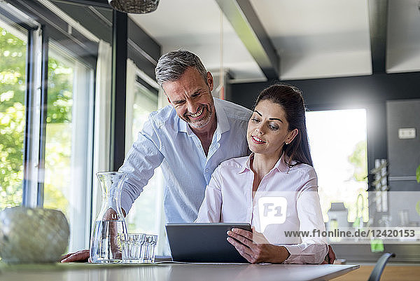 Happy couple at table at home sharing a tablet