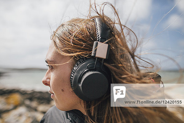 France  Brittany  Landeda  woman wearing headphones at the coast
