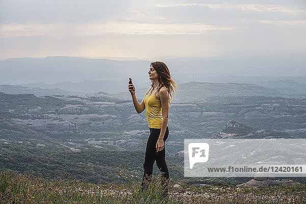 Spain  Barcelona  young woman taking selfie on Montcau Mountain