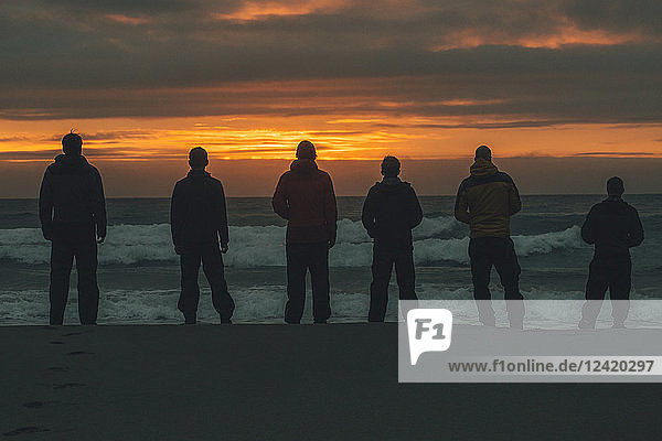 Norway  Lofoten  Moskenesoy  Young men standing at Bunes Beach at sunset