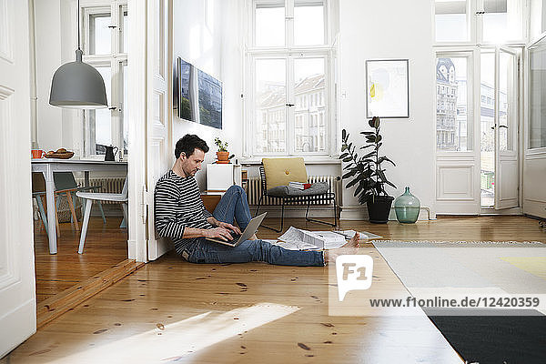 Man sitting in foor  using laptop  working from home