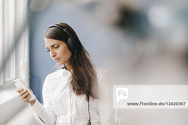 Young woman using smartphone  wearing headset