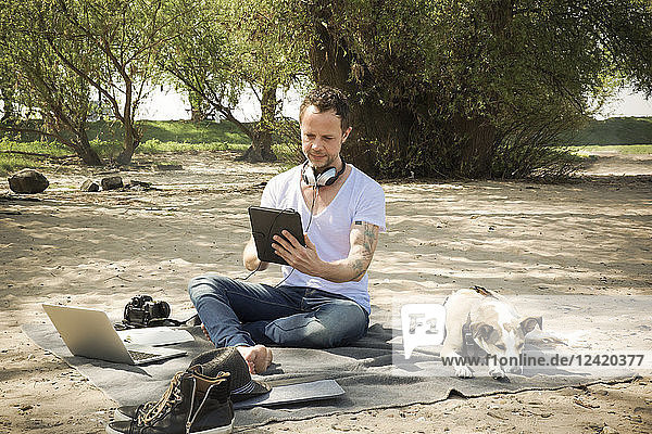 Man with dog sitting on blanket at a beach using tablet