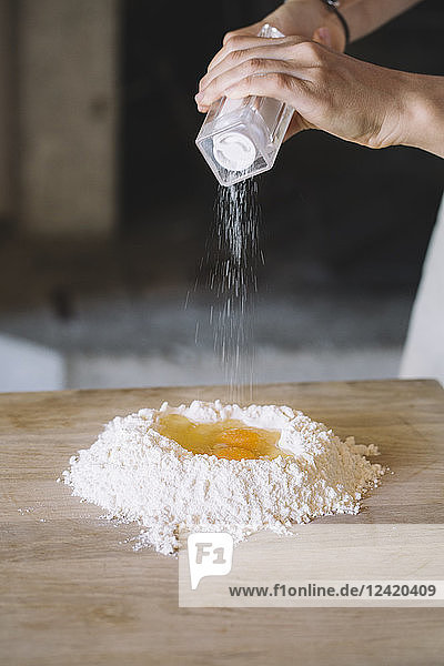 Woman salting eggs and flour on pastry board