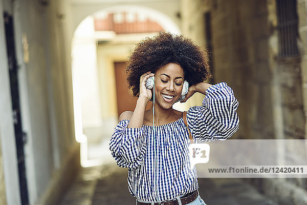 Portrait of happy young woman listening music with headphones