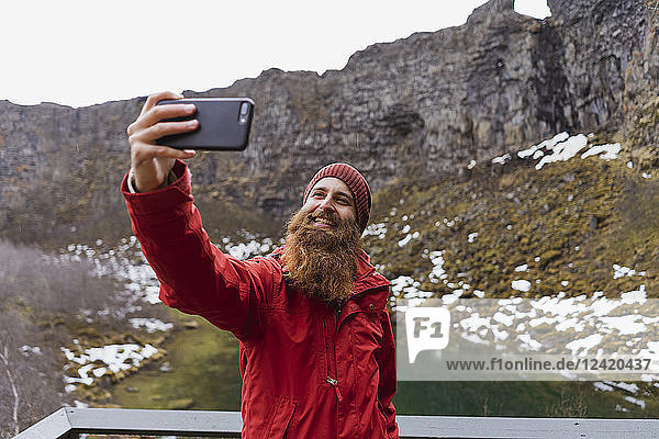 Iceland,  smiling bearded man using smartphone,  selfie