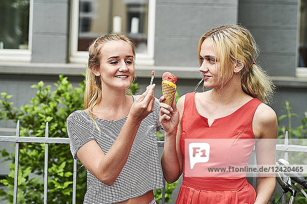 Two young women sharing an ice cream cone in the city